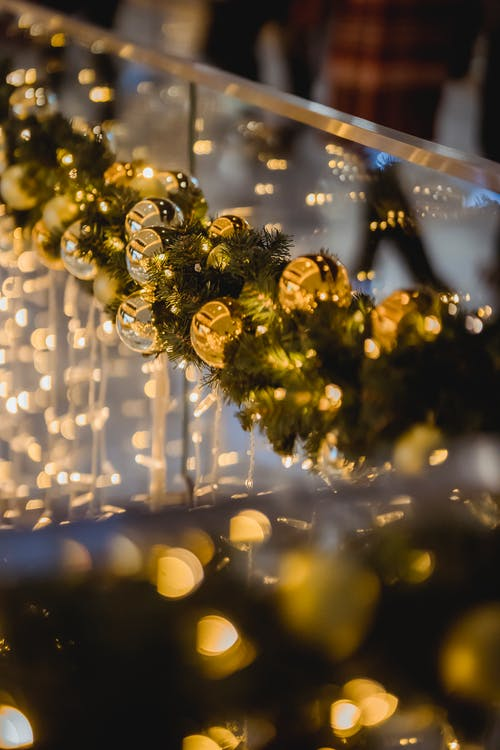 Green garland of spruce with glowing lights and baubles hanging on glass on blurred background