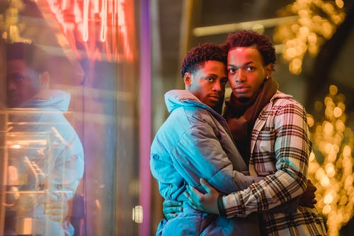 Happy African American couple of homosexual men hugging near window with neon glowing lights on blurred background of street