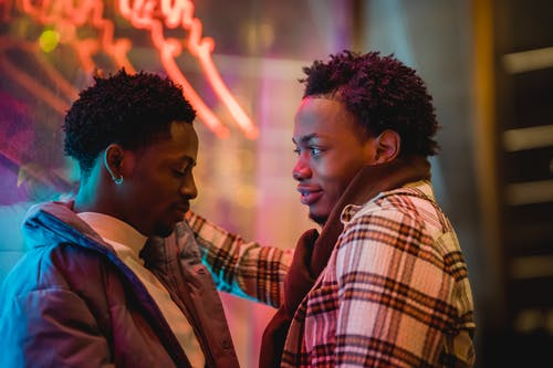 Side view of African American homosexual men speaking and smiling while leaning on window with neon lights