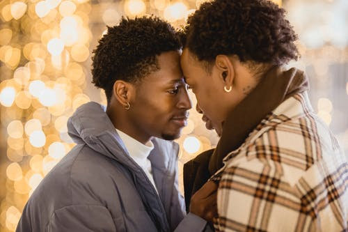Side view of happy African American homosexual couple of men touching foreheads on blurred background of glowing lights