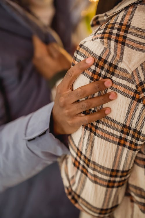 Black friends conflicting and arguing while touching jackets
