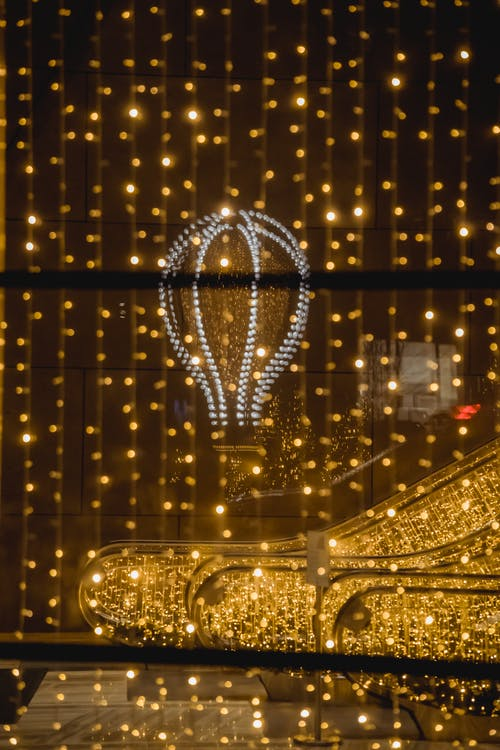 Shimmering lights of hanging garland and luminous air balloon on festive special event