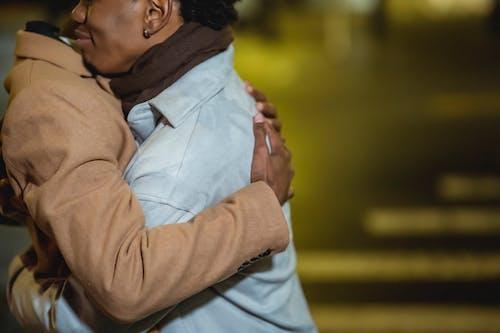 Black homosexual couple cuddling on street