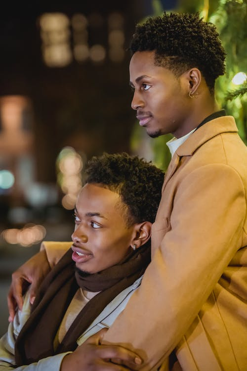 Side view of African American male couple in outerwear hugging gently and attentively looking away against lights