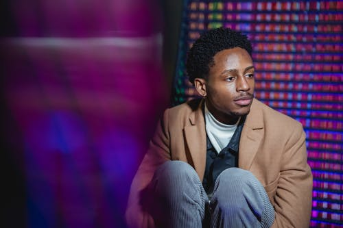 Serious black man sitting against metal wall with bright lights