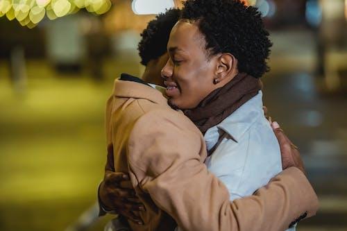 Smiling black same sex couple embracing on street
