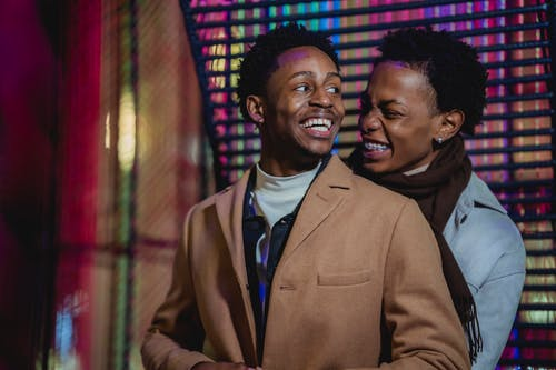 Cheerful black gay couple embracing and laughing happily