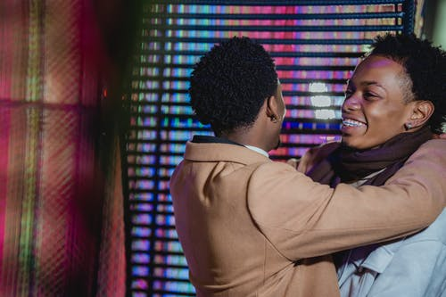 Side view of African American homosexual couple enjoying romantic moment and laughing happily against blurred lights