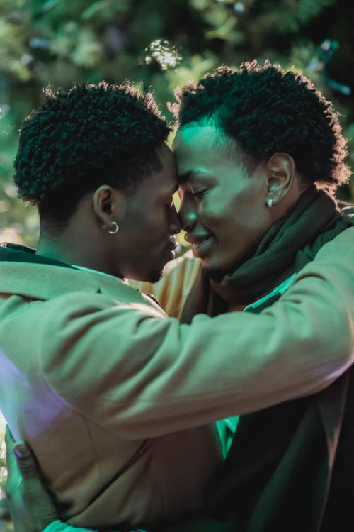 Side view of African American gay lovers caressing gently and embracing each other against Christmas tree