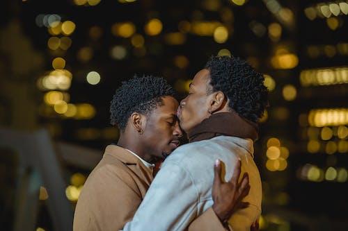 Black loving gay kissing forehead of boyfriend