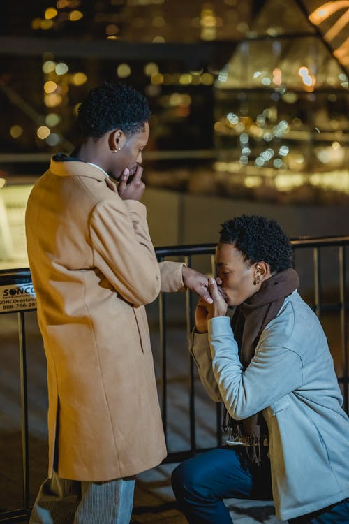 Side view of African American gay kneeling while making proposal and kissing hand of to boyfriend covering mouth at night