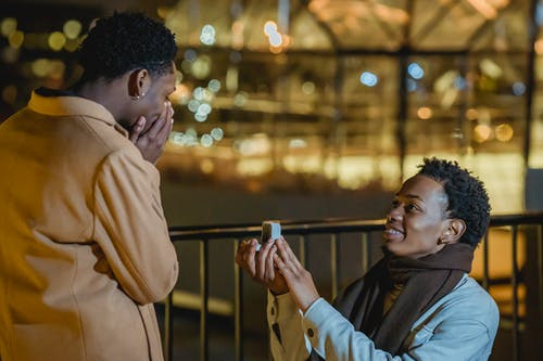 Side view of African American knelling and doing proposal to amazed homosexual lover at night