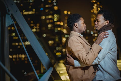 Side view of confident young African American homosexual men in warm clothes standing and embracing in city street on building roof at night while looking at each other
