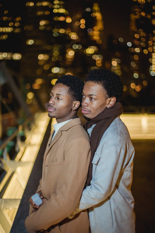 Side view of confident young African American homosexual men in warm clothes standing and embracing on building roof in city street near metal constructions at night while looking away