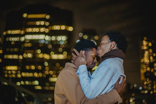 Black homosexual male couple kissing while cuddling in city street