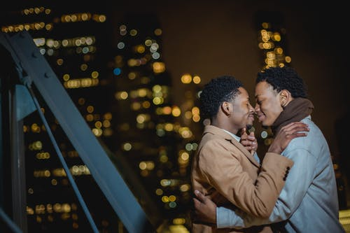 Side view of smiling young African American gay couple in outerwear hugging with closed eyes while standing in city street on building roof at night