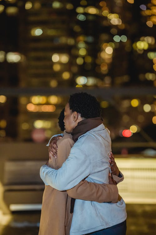 Black homosexual male couple cuddling in glowing city street