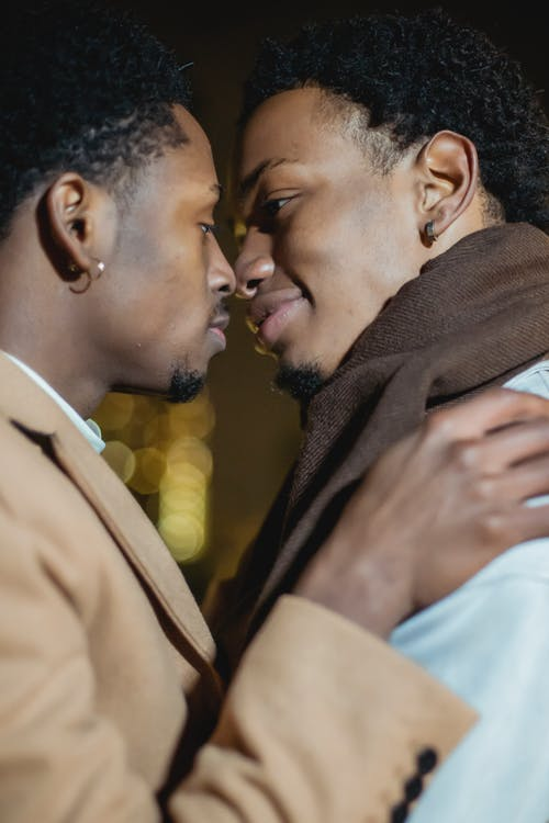 Black gay couple hugging in city street at night