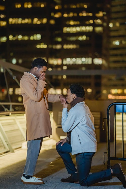 Black homosexual male couple making marriage proposal on rooftop