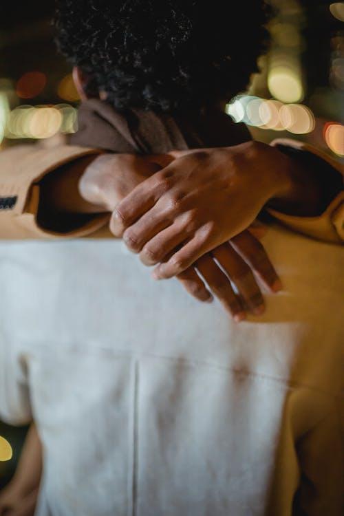 Crop black man hugging anonymous partner