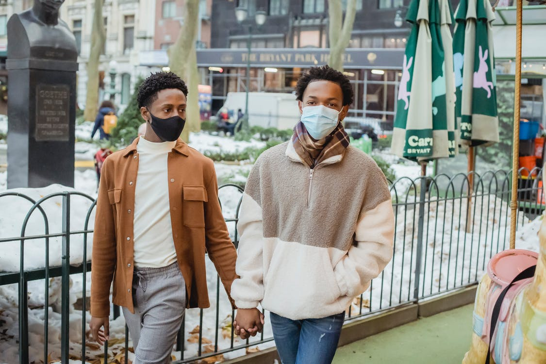 Gentle African American homosexual couple wearing casual wear in protective masks holding hands while strolling on street during coronavirus pandemic in city