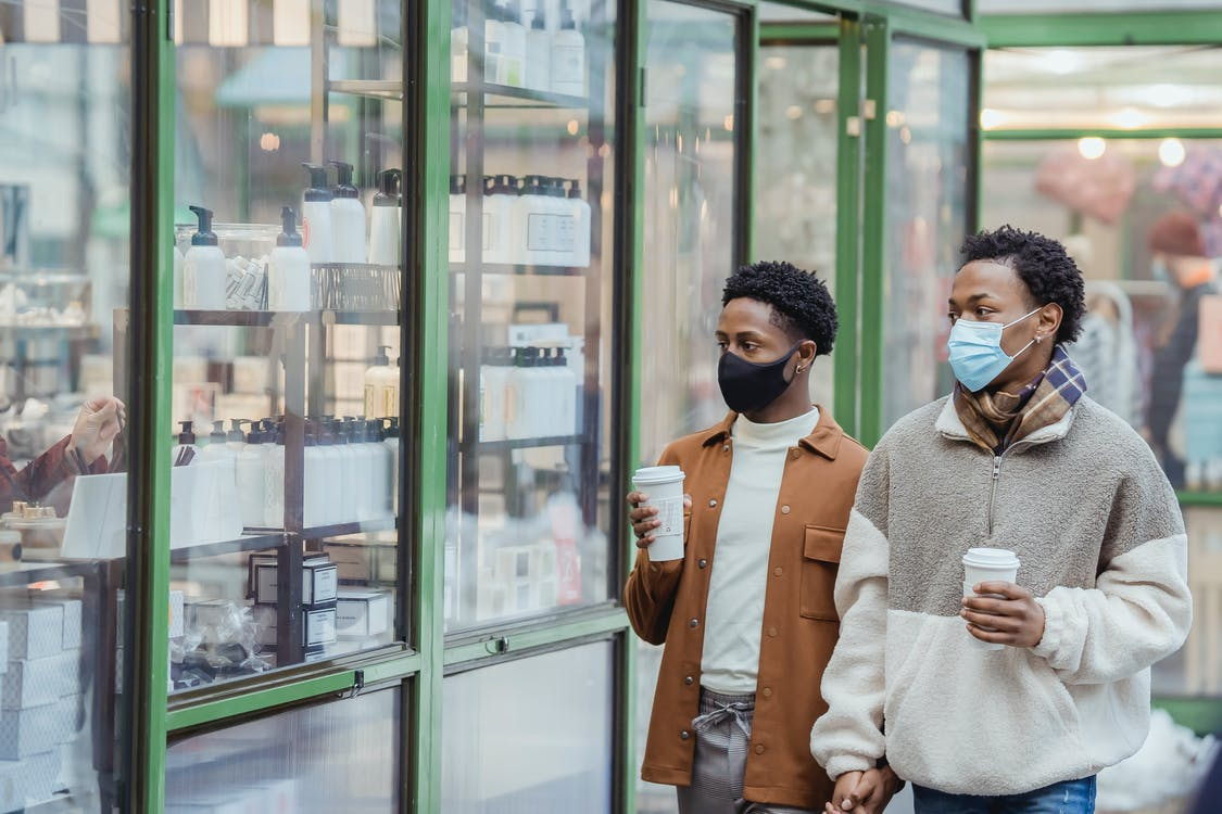 African American homosexual couple with takeaway beverages in medical masks holding hands while strolling on street near glass case of store in city