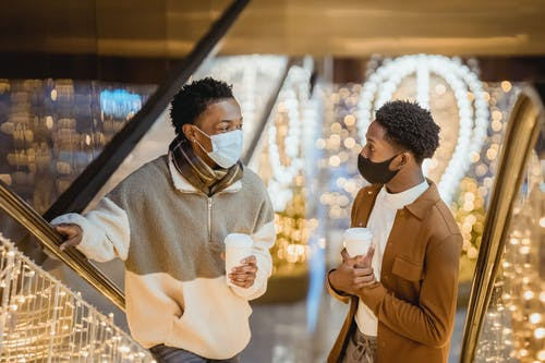 African American male partners in cloth face masks with hot drinks to go speaking and looking at each other