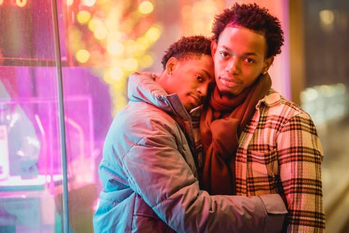 Beloved young ethnic guys hugging on city street at night