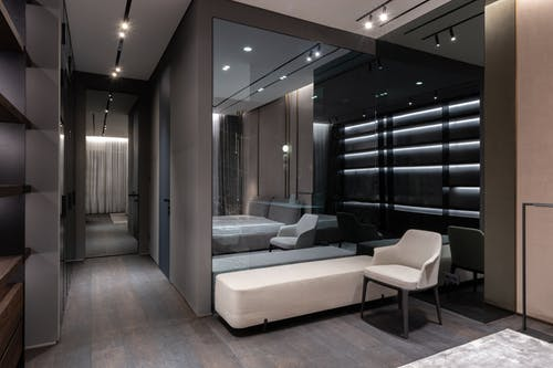 Interior design of bedroom with modern furniture and big mirror on wall in flat