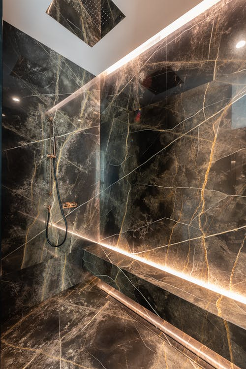Shower in stylish bathroom with marble walls