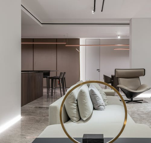 Comfortable soft couch with cushions and dining zone in kitchen in modern studio interior