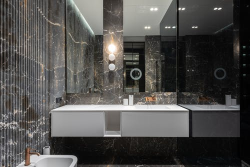 Interior design of modern stylish bathroom with big mirrors and white ceramic tub near sink