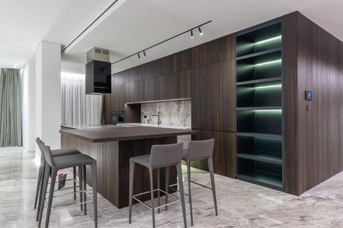 Modern interior design of contemporary spacious kitchen with dining zone and wooden furniture in apartment