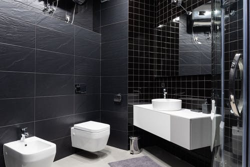 Interior design of modern bathroom with sink and bidet with mirror and decorated with black tile