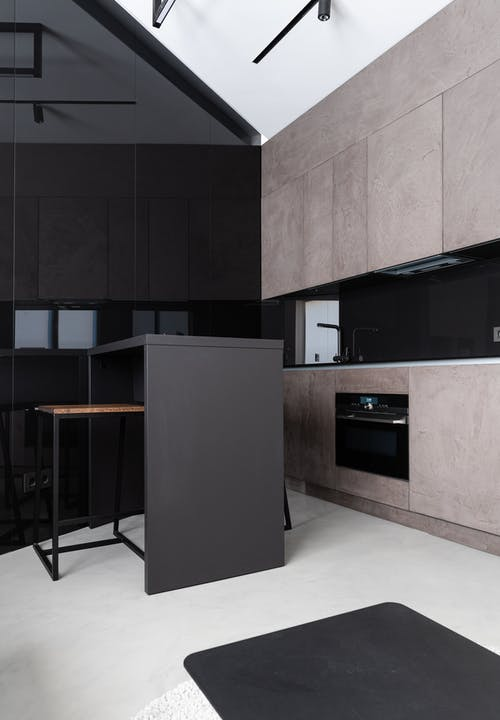 Interior design of contemporary spacious kitchen with dining table and oven in modern apartment