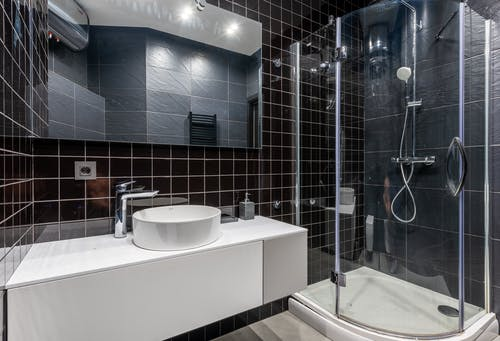 Interior of stylish modern bathroom with ceramic sink and shower unit with transparent glass doors and mirror