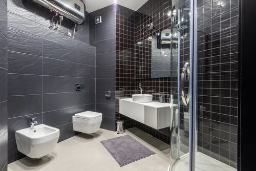 Interior design of modern bathroom with shower and bidet decorated with black tile