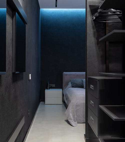 Interior of contemporary bedroom with big comfortable bed with pillows and opened wardrobe with shelves and desks