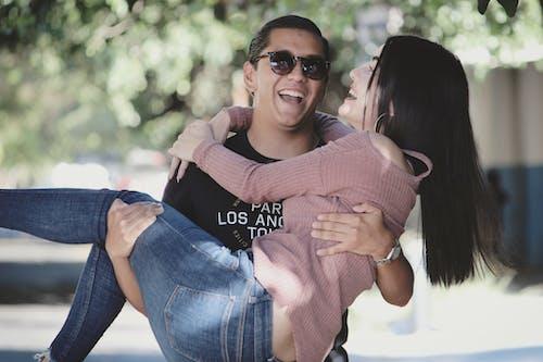 Man in Black Sunglasses Hugging Woman in Pink Sweater