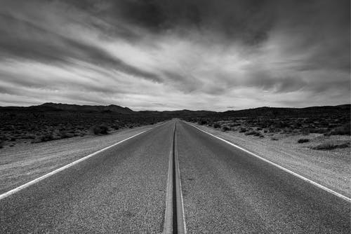 Grayscale Photo of Road Under Cloudy Sky