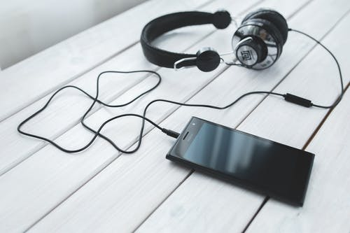 Black smartphone and headphones on a desk