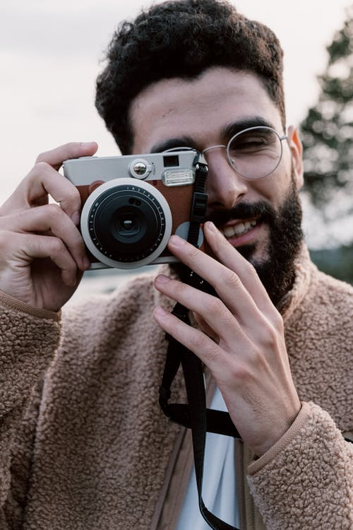 Photo of a Man Wearing Eyeglasses Using an Analog Camera