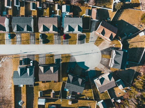 Drone view of residential district with modern houses and yard on sunny day in summer