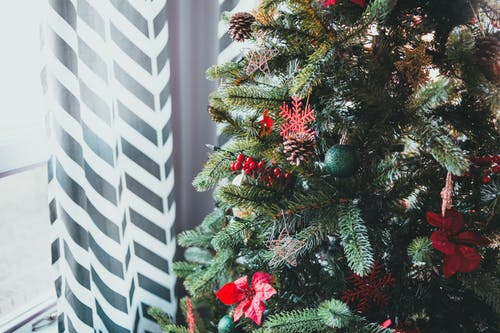 Christmas tree decorated with toys standing near window with patterned curtain on daylight in winter