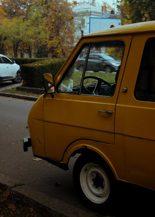 Retro van of yellow color parked on asphalt road on city street in autumn