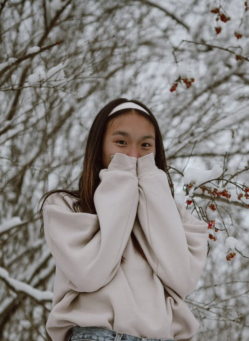 Unrecognizable gentle Asian woman against snowy tree in park