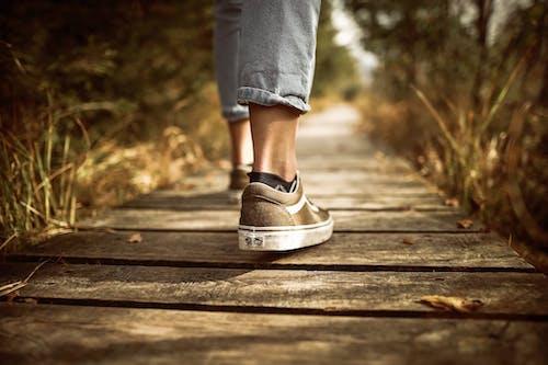 Gratis arkivbilde med fottøy, gå, gress, joggesko