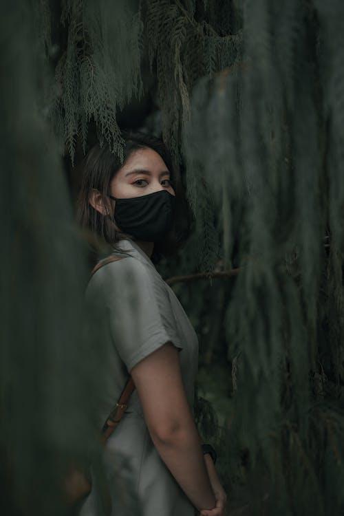 Side view of female in mask with backpack standing near trees with green foliage in daytime in woods while looking at camera