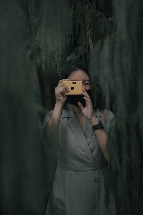Anonymous female in mask standing near trees with green foliage while taking photo on analog camera in daytime in nature