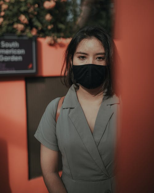 Lady in mask standing near red fence and trees in daytime in street while looking at camera